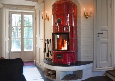 Wine-red tiled stove, created for a low energy house